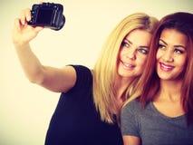 拍与照相机的两个模型女孩自已照片 免版税库存图片