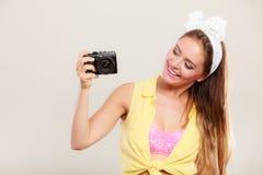 拍与照相机的女孩妇女的Pin照片 免版税库存图片