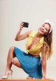 拍与照相机的女孩妇女的Pin照片 免版税图库摄影