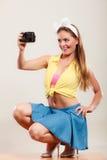 拍与照相机的女孩妇女的Pin照片 免版税库存照片