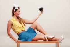 拍与照相机的女孩妇女的Pin selfie照片 免版税库存照片