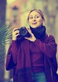 拍与照相机的女孩照片在镇 免版税库存图片