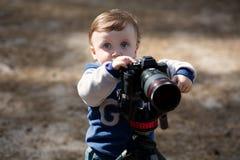 拍与照相机的年轻摄影师孩子照片在三脚架 免版税库存照片