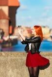 拍与照相机老镇格但斯克的时兴的旅游女孩照片 免版税图库摄影