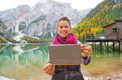 拍与片剂个人计算机的愉快的少妇照片在湖braies 库存图片