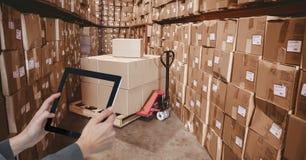 拍与片剂个人计算机的手照片在仓库里 图库摄影