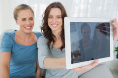 拍与片剂计算机的朋友照片 免版税图库摄影
