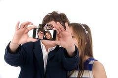 拍与电话的两个愉快的少年人一张照片 免版税库存图片