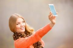 拍与电话的女孩自已照片户外 免版税库存照片