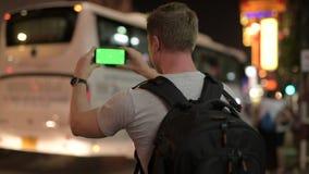 拍与电话的年轻旅游人背包徒步旅行者背面图照片在唐人街在晚上 影视素材