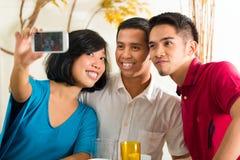拍与移动电话的亚裔朋友照片 免版税图库摄影