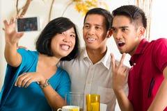 拍与移动电话的亚裔朋友照片 免版税库存照片