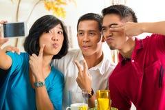 拍与移动电话的亚裔朋友照片 免版税库存图片