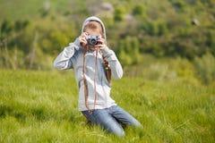 拍与老照相机的小十几岁的女孩照片 免版税库存照片