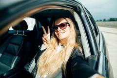 拍与聪明的电话照相机的微笑的少妇selfie照片室外在汽车 免版税库存照片