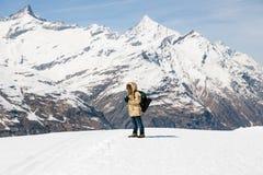 拍与葡萄酒影片照相机的一个人一张照片在雪在雪山背景中  免版税图库摄影