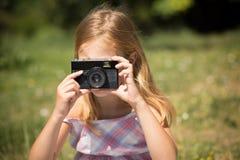 拍与葡萄酒照相机的小女孩照片 免版税库存照片
