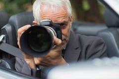 拍与他的专业照相机的无固定职业的摄影师照片 免版税库存照片