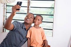 拍与他的电话的父亲和儿子照片 库存图片