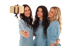 拍与他们的电话的3名微笑的妇女一张selfie照片 库存图片