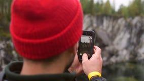 拍与hir智能手机的雨夹克的远足者人照片户外 使用手机app的行家拍照片与 影视素材