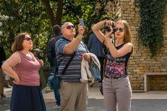 拍与MOBIL电话和照相机的两名妇女和一个人照片在布达佩斯匈牙利 库存照片