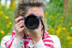 拍与SLR照相机的妇女照片 免版税库存图片