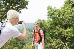 拍人的照片有摆在细胞巧妙的电话、迁徙的年轻人和妇女的山风景的背包的女孩 免版税库存图片