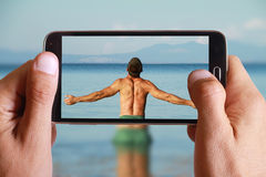 拍人的照片男性手举站立他的手或开放的胳膊回顾对海与细胞,手机的蓝天天际 免版税库存图片