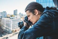 拍从大厦阳台的调查员或私家侦探或者记者或者无固定职业的摄影师照片与专业照相机的 库存照片