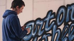 拍他的在电话的墙壁街道画的照片年轻人 免版税库存照片