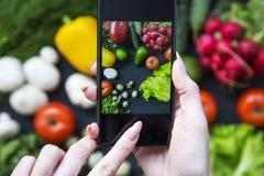 拍健康食物的照片与她的智能手机的女孩 免版税库存照片