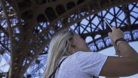 拍全景照片的愉快的妇女在埃菲尔铁塔下 影视素材