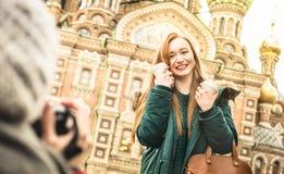 拍冬天旅行照片的愉快的女朋友在旅行 免版税库存照片