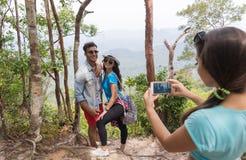 拍加上的照片女孩摆在细胞巧妙的电话,迁徙的年轻人的山风景的背包和 免版税库存图片