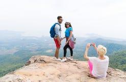 拍加上的照片女孩摆在细胞巧妙的电话,迁徙的年轻人的山风景的背包和 免版税库存照片