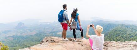 拍加上的照片女孩摆在细胞聪明的电话全景的山风景的背包,迁徙的年轻人 免版税库存图片