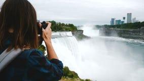 拍史诗尼亚加拉大瀑布视图慢动作的照片激动的旅游妇女和照相机后面看法有背包的 股票视频