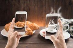 拍咖啡杯和新月形面包照片在木背景 免版税库存图片