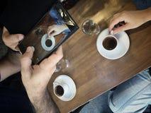 拍咖啡杯照片有智能手机的 免版税库存照片