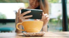拍咖啡茶的照片在智能手机的一个少妇,拍摄与流动照相机的膳食 影视素材