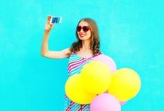 拍在一个智能手机的愉快的微笑的妇女一张照片有空气五颜六色的气球的 免版税库存图片