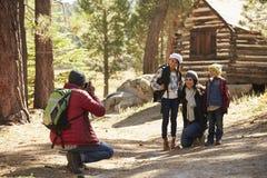 拍在一栋原木小屋前面的家庭一张照片在森林里 免版税库存图片