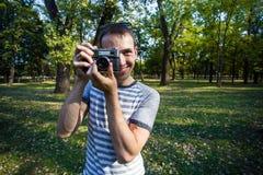 拍在减速火箭的照相机的年轻人照片 库存图片