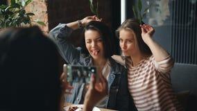 拍在咖啡馆的女性朋友照片摆在与鬼脸使用智能手机 股票录像