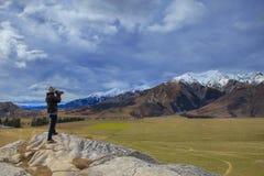 拍在城堡小山图po岩石峭壁的摄影师一张照片  库存照片