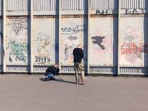 拍在墙壁街道画的愉快的夫妇一张照片 免版税库存图片