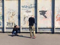 拍在墙壁街道画的愉快的夫妇一张照片 免版税库存照片