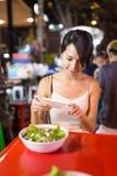 拍在她的食物的妇女照片在室外市场上在曼谷市 免版税图库摄影