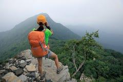 拍在山上面的远足者照片  免版税库存图片